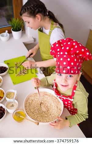 Happy sisters cooking together. Young happy children kids family having fun preparing granola in kitchen at home - stock photo