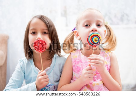 happy sisters have colored lollipops
