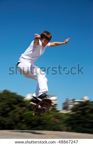 Happy skateboarder on a jump - stock photo