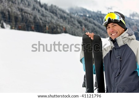 happy skier smiling with his skiis in the trail - stock photo