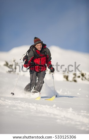 Happy skier with knit hat skiing downhill in deep snow