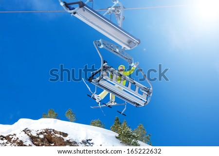 Happy skier young woman sit on the ski lift and waiving hand looking back - stock photo