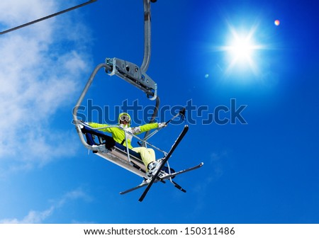 Happy skier young woman sit on the ski lift and waiving hand with sky on background