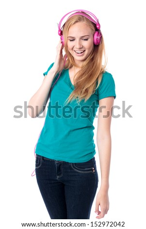 Happy slender trendy young woman standing listening to music on her headphones with a smile of pleasure on her face