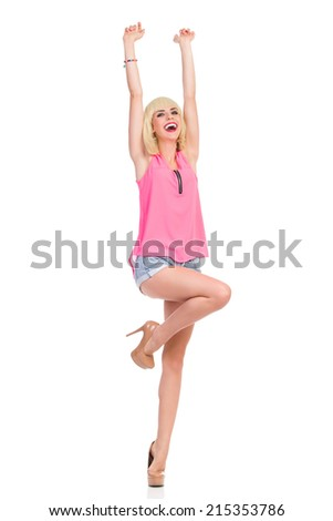 Happy slim girl. Smiling blond young woman in high heels and pink top standing on one leg with arms raised. Full length studio shot isolated on white. - stock photo