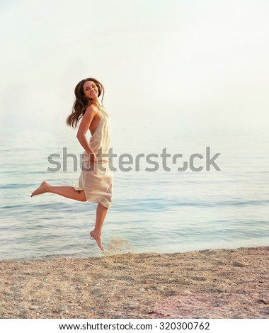 Happy slim woman dressed in white dress jumping against sea backdrop. - stock photo