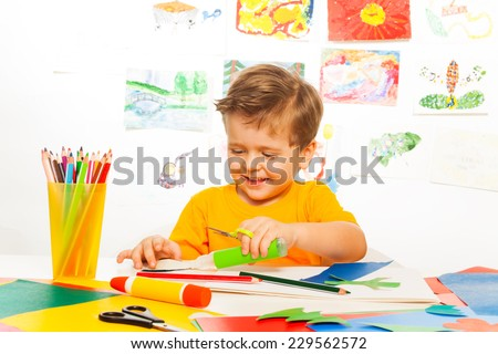 Happy small boy crafts with scissors, paper, glue - stock photo