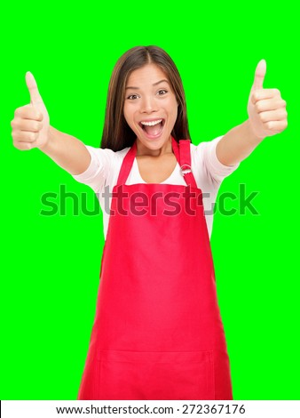 Happy small business owner excited in red apron showing thumbs up success sign isolated cutout on green chroma key background. - stock photo