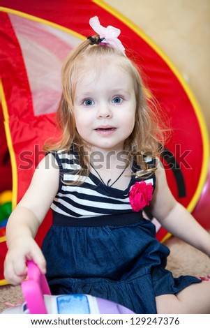 Happy small child playing in domestic room - stock photo