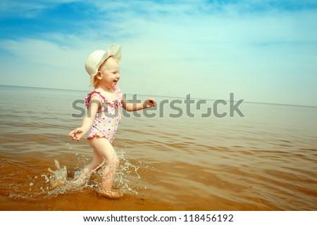 happy small girl running on the beach - stock photo
