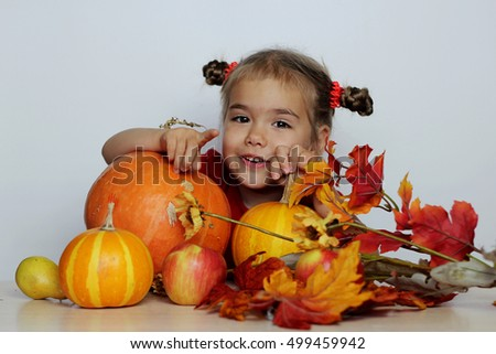 Happy small girl with pumpkins and other agriculture harvested products over white background, Thanksgiving Day and Halloween concept, indoor portrait
