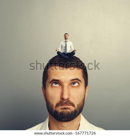 happy small man resting on the big head man - stock photo