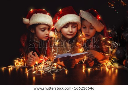 Happy small three girls in Santa hats have a Christmas - stock photo
