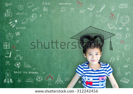 Happy smart Asian child girl w/ big graduation cap/ hat on green color chalkboard background w/ freehand chalk drawing doodle & copy space: Smiling female little bright scholar brain kid on blackboard - stock photo