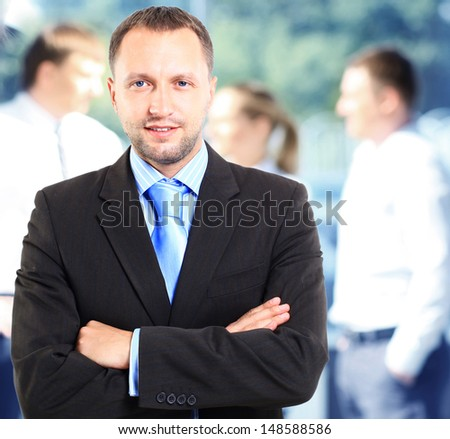 Happy smart business man with team mates discussing in the background  - stock photo