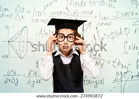 Happy smart schoolgirl in big glasses and academic hat performs the task at the blackboard. Education. - stock photo