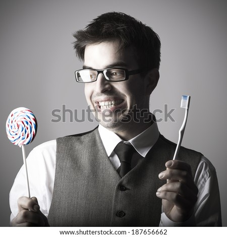 Happy smart young man with a lollipop in one hand and a toothbrush in the other against grey background - stock photo