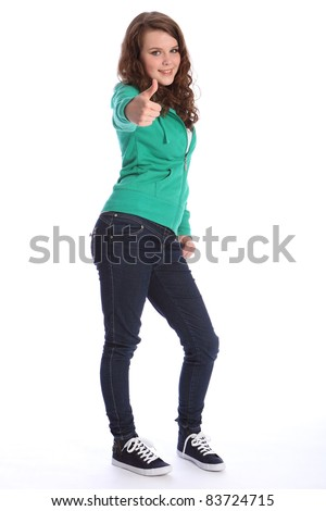 Happy smile from pretty teenager school girl with long brown hair, giving a thumbs up positive hand sign. She is wearing dark blue jeans and a green sweater.