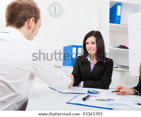 happy smile young attractive business woman and man handshaking at office desk, businessman and businesswoman shaking hands with partner in meeting or signing contract, businesspeople set deal - stock photo