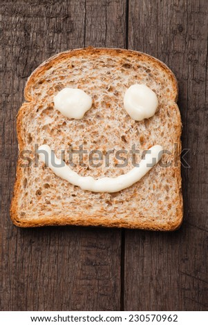 Happy smiley made from mayonnaise on slice of bread - stock photo