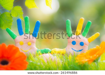 Happy smiley on hands against green spring background - stock photo