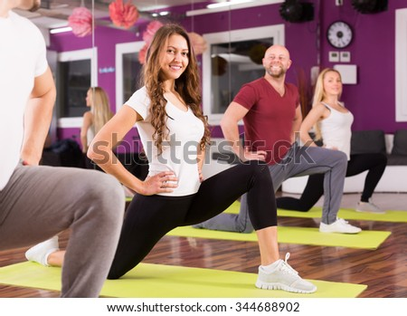 Happy smiling adults having group fitness class in sport club - stock photo