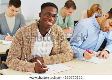 Happy smiling african student taking notes in university class - stock photo