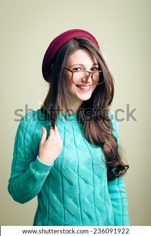 happy smiling and looking at camera studio portrait of hipster or hippie young beautiful woman having fun in big glasses wearing knitting jumper over copy space background  - stock photo