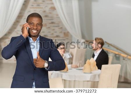Happy smiling Asian businessman speaking over mobile phone and showing thumb-up or okay sign while his partners sitting at table behind him.