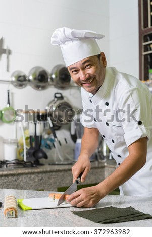 Happy smiling asian chef make rolls (sushi) on the kitchen. - stock photo
