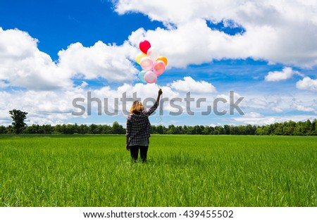 Happy smiling Asian woman holding balloons holding the middle of every green. beautiful sky - stock photo