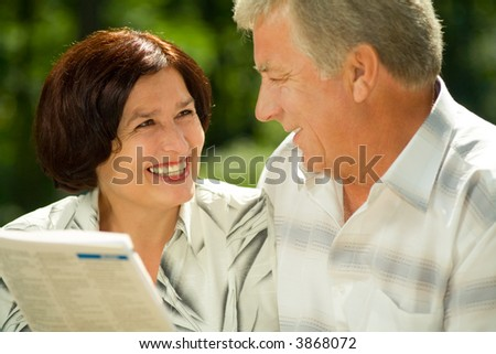 Happy smiling attractive elderly couple reading together outdoors