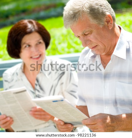 Happy smiling attractive senior couple reading together, outdoors - stock photo