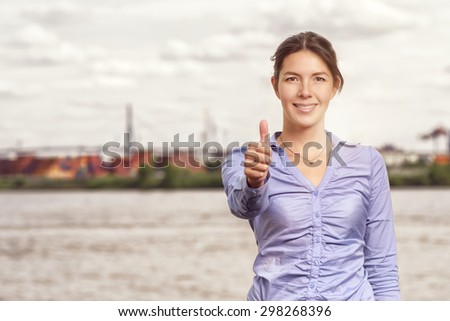 Happy smiling attractive woman giving a thumbs up gesture of success and approval, upper body portrait in front of an urban river or waterway with copyspace - stock photo