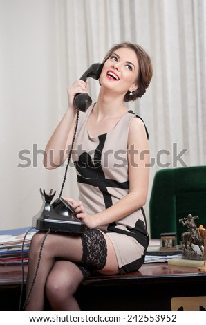 Happy smiling attractive woman wearing an elegant dress and black stockings talking by phone in an office scenery. Beautiful young sensual female with short dress sitting on desk holding the phone - stock photo