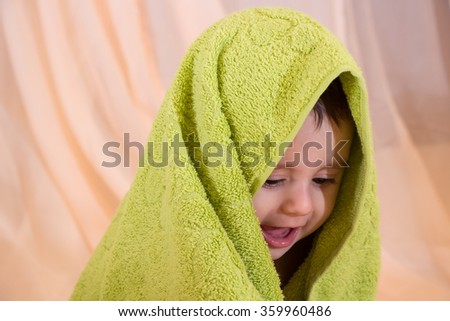 Happy smiling baby boy with a green towel on his head - stock photo