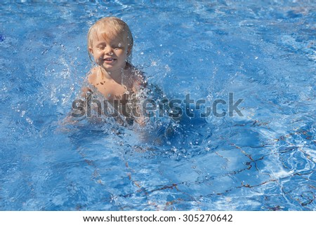 Happy smiling baby has fun jumping with splashes in blue water in pool before swimming lessons. Healthy lifestyle, active parents, and people water sports activity on summer family vacation with baby. - stock photo