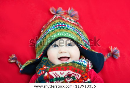 Happy smiling baby in a funny colorful hat and scarf - stock photo