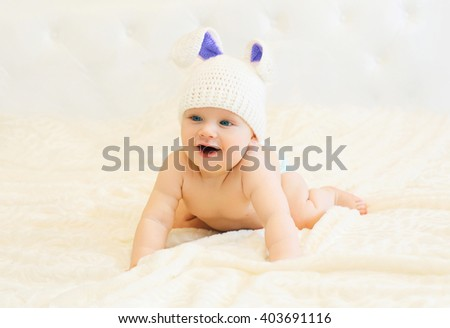 Happy smiling baby in knitted hat with a rabbit ears crawls on bed - stock photo