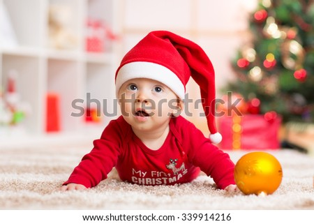 Happy Smiling baby lying against domestic festive backdrop with Christmas tree. Cute kid wearing Christmas Santa hat and suit - stock photo