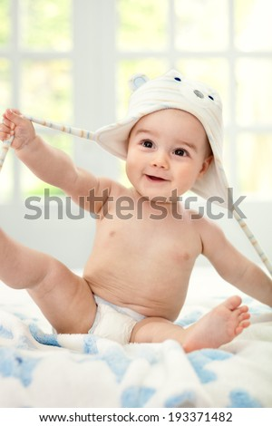 Happy smiling baby with bear cap - stock photo
