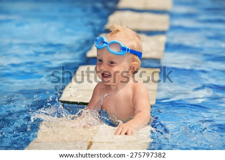 Happy smiling baby with underwater goggles is having fun playing with splashes in blue water in pool before swimming lessons. Lifestyle and summer children activity in vacation in tropical resort - stock photo