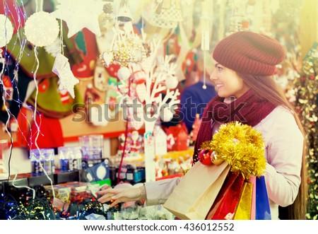 Happy smiling beautiful brunette choosing Christmas decoration at market - stock photo