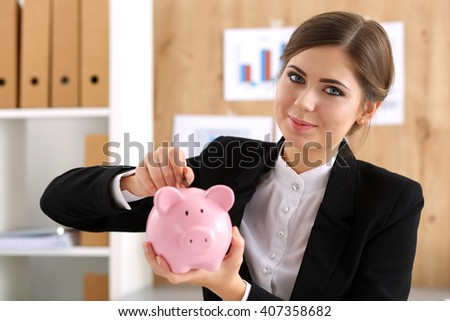 Happy smiling beautiful businesswoman putting pin money into pink pig. Future needs loan, education or mortgage credit, spend vacation of dream, effective buying, financial risk and safety concept