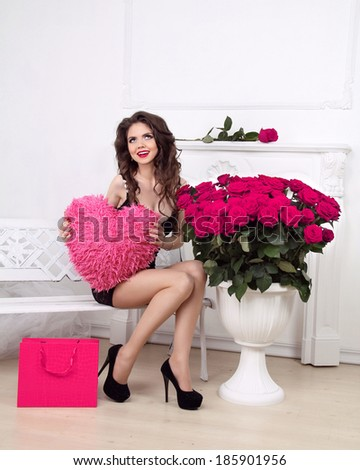 Happy smiling beautiful girl holding heart over pink bouquet of roses and shopping gift. Valentine day love concept. - stock photo