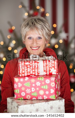 Happy smiling beautiful senior lady with a stack of Christmas gifts sitting in front of a decorated Christmas tree with a bokeh of twinkling lights - stock photo