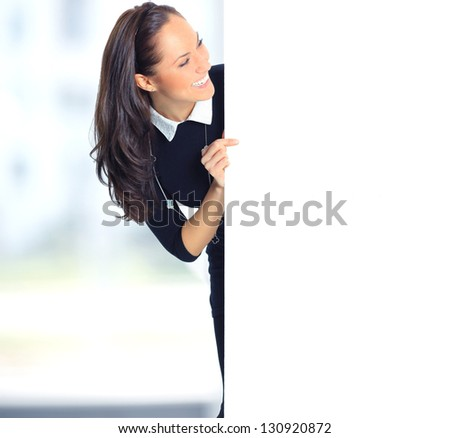 Happy smiling beautiful young business woman showing blank signboard - stock photo