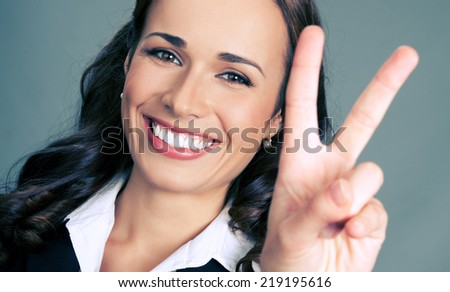 Happy smiling beautiful young business woman showing two fingers or victory gesture, over gray background - stock photo