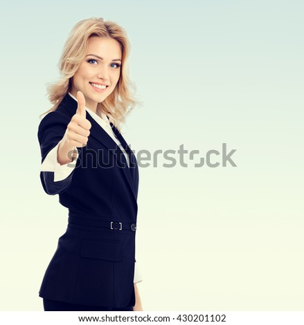 Happy smiling beautiful young businesswoman showing thumbs up gesture, with blank copyspace area for text or slogan - stock photo