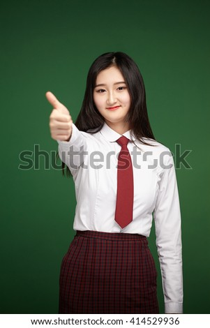 Happy smiling beautiful young student woman showing thumbs up gesture, green background - stock photo